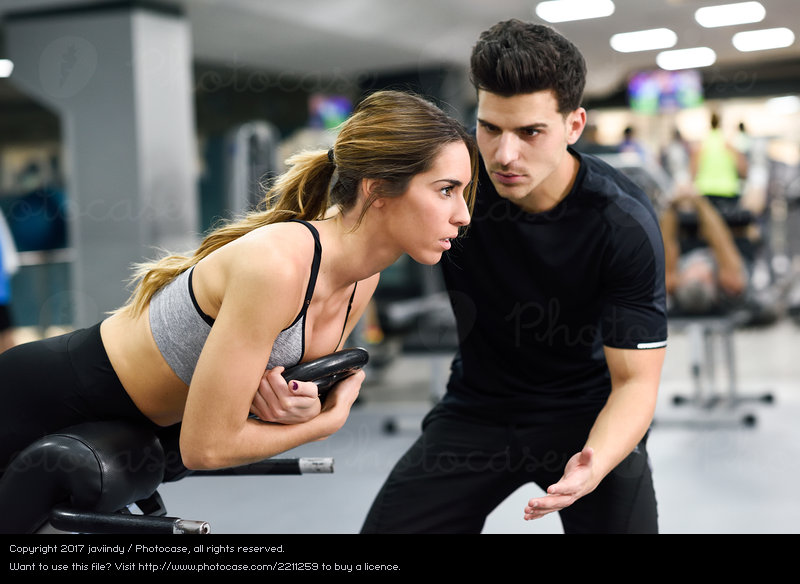 2211259-personal-trainer-helping-young-woman-lift-weights-woman-photocase-stock-photo-large